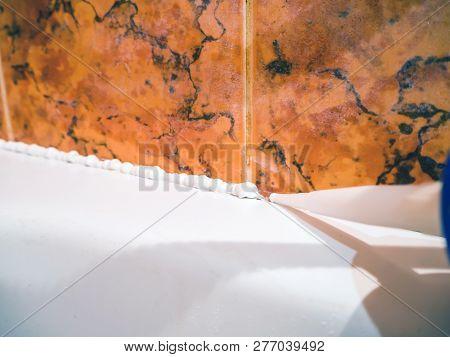 Close Up Of Caulking Bath Tube With White Silicone Hermetic. Plumber Caulking Bathtub With Silicone