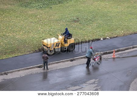 Road Construction Worker Compactes Fresh Asphalt With Roller Compactor Machine. Another Worker Overw