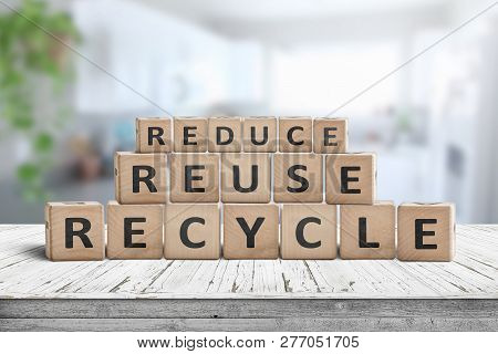 Reduce, Reuse And Recycle Sing On A Wooden Desk Woth A Fresh Bright Background