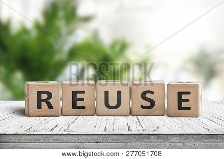 Reuse Sign On A Wooden Table In A Room With Green Plants In Bright Light