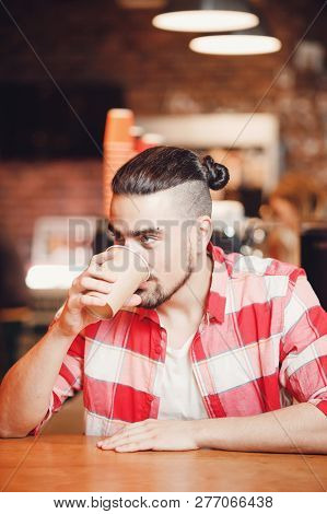 Stylish Informal Young Man With Piercing And Long Dark Hair Plaid Shirt, Drinking Coffee At Lunch Br