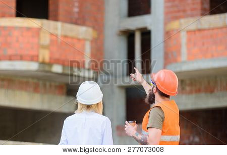 Construction Team Communication Concept. Discussing Plan. Woman Engineer And Builder Communicate At