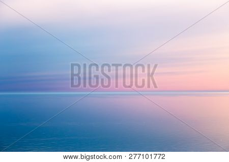 Idyllic Seascape With Pink Evening Color. The Calm Sea Reflects The Clear Sky Like A Mirror. Blue Pi