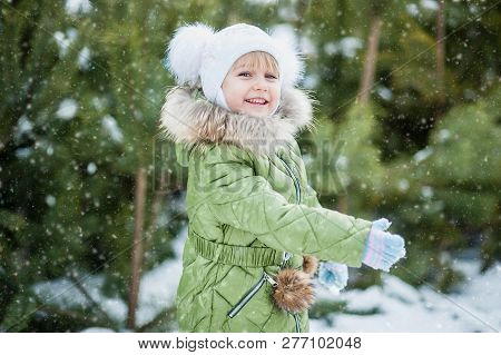 Girl Playing Snowballs. Funny Little Girl Having Fun In Winter Park. Making Snowballs Happy Child Gi