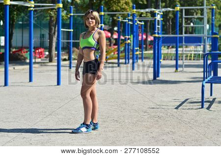 A Young Caucasian Athlete Girl In A Bright Green Sportswear Stands Against The Backdrop Of A Street