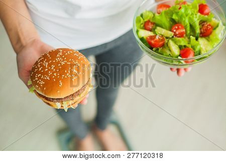 Diet. Woman Measuring Body Weight On Weighing Scale Holding Burger And Salad. Sweets Are Unhealthy J