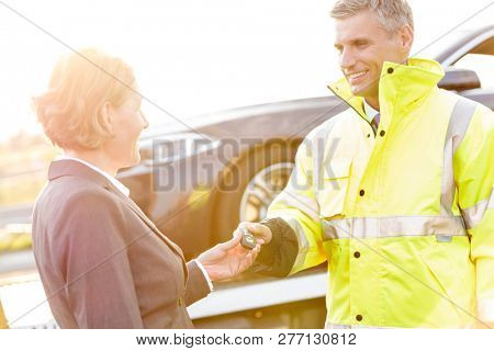Smiling tow truck driver giving car key to businesswoman