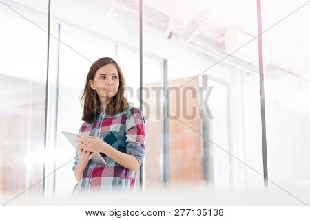 Thoughtful businesswoman holding digital tablet in office