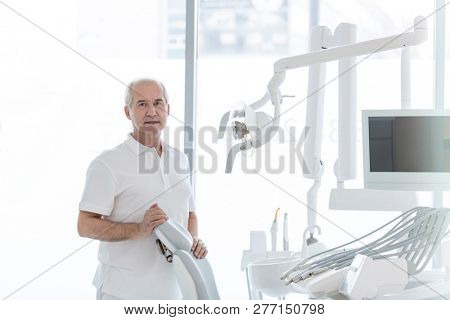 Portrait of senior dentist standing by chair at dental clinic