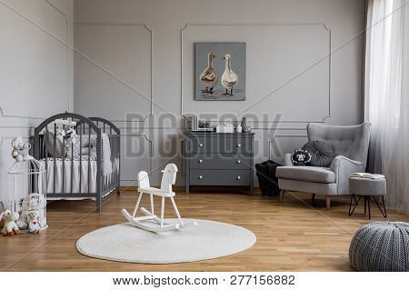 White Rocking Horse On Rug In Grey Baby's Bedroom Interior With Poster Above Cabinet. Real Photo