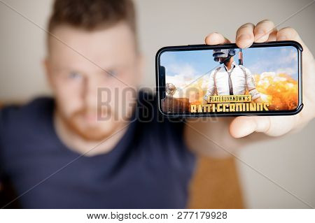 Moscow, Russia - January 1, 2019 : Man Holding Smartphone With Player Unknown Battleground Pubg Onli