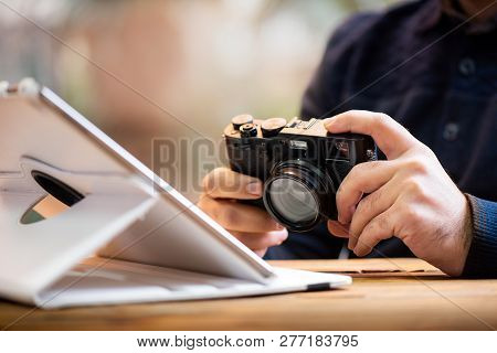 Photographer Working On Tablet And Holding His Digital Range Finder Camera