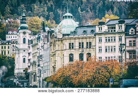 Karlovy Vary town with Church of Saint Mary Magdalene, Czech republic. Autumn scene. Travel destination. Analog photo filter with scratches. poster