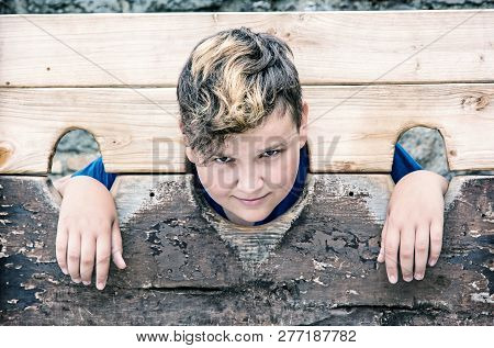 Young Caucasian Boy In Medieval Pillory. Misery Theme. Punishment Device. Blue Photo Filter.