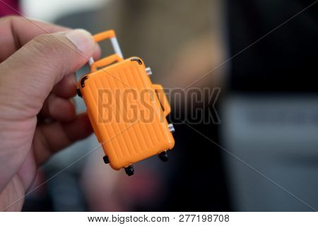 Miniature Of Orange Suitcase In Hand : Ready For Travel