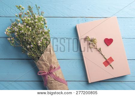 Bouquet Of Flowers Tied With A Red Bow And A Pink Notebook On A Blue Wooden Table. Valentines Day Fl
