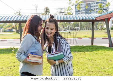 Two Young Beautiful Smiling Girlfriends Tells A Brunette Story Or Gossip In Her Ear. Two Woman Frien