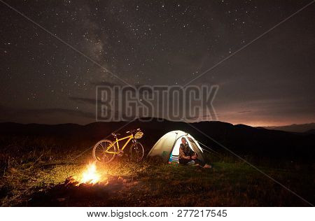 Young Woman Traveller Having A Rest At Night Camping Near Burning Campfire, Illuminated Tourist Tent