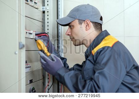 Electrician at work using a tester on an industrial panel in a factory