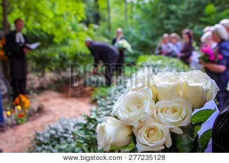 Roses In Cemetery With People In The Background. Funeral In Cemetery;  White Roses In Cemetery. Pray
