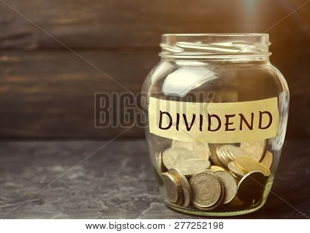 Glass Jar With The Word Dividend. A Dividend Is A Payment Made By A Corporation To Its Shareholders
