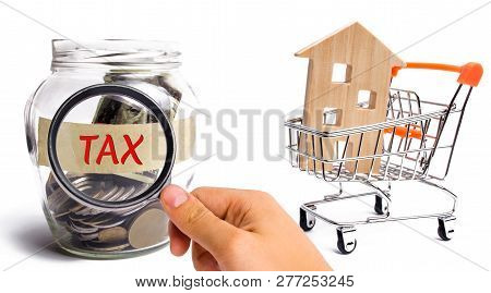 Glass Jar With Coins And The Inscription Tax And House. Payment And Repayment Of Taxes To The State.