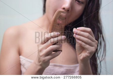 Hair Loss And Hair Care. Hands Holding A Comb And Hair. The Girl Is Combing Her Hair In The Bathroom