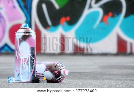 Several Used Spray Cans With Pink And White Paint And Caps For Spraying Paint Under Pressure Is Lies