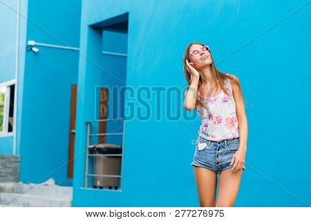 Horizontal Portrait Of Cute Stylish Girl On Blue Background Standing And Listening To Music On Earph