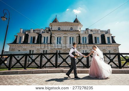 Russia,orenburg -july 29,2017: The Bride And Groom Holding Hands Walking Near The Beautiful Building