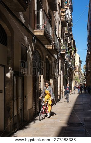 Barcelona, Spain - March 28, 2018: Unidentified woman riding bicycle on the streets of Barcelona. Bicycle as urban transport in Barcelona