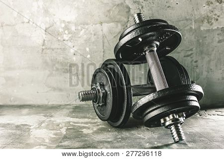 Closeup Shot Of Two Dumbells Placed On Dark Grey Surface.