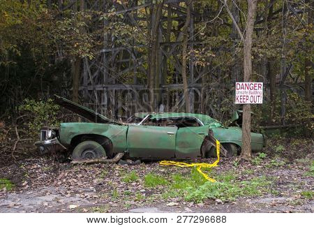 Old Car Left To Rot Beside a Wooden Roller Coaster in an Abandoned Amusement Park poster