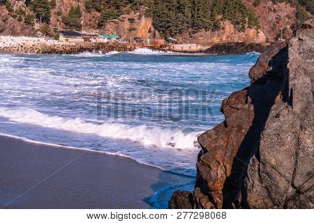 Whitecaps On Waves Coming Into Shore With Large Volcanic Rock Formations In Foreground On Clear Sunn