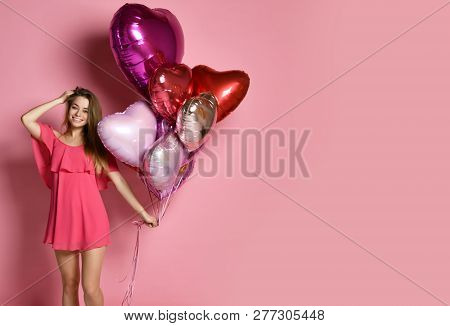 Valentine Beauty Girl Hold Red And Pink Air Balloons Laughing On Pink Background. Beautiful Happy Yo