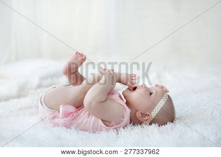 Cute Adorable Baby Girllying Alone Dressed On A White Bed.little Child Looking At The Camera .baby L