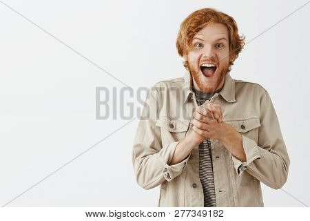 Charmed And Thrilled Expressive Redhead Male Fan In Outdoor Jacket Clenching Palms Near Chest Gaspin
