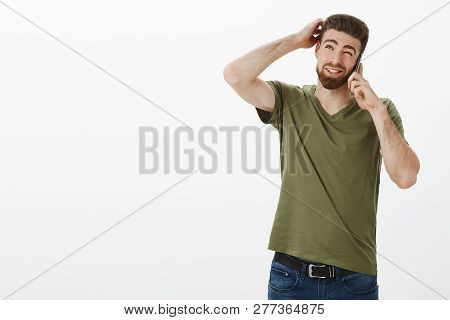 Let Me Think. Cute Man With Beard Making Plans As Talking To Friend Via Smartphone Being Unsure Thin