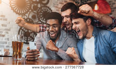 Diverse Football Fans Watching Football On Smartphone And Celebrating Victory Score In Pub
