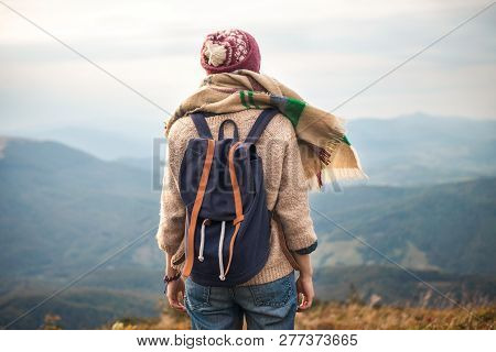 Hiker Woman Wearing In Warm Clothing  With Backpack Hiking In The Mountains, Relaxing And Enjoying A