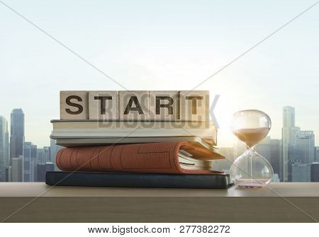Wooden Blocks With The Word Start, Notebook, Books And Sand Clock On Table With Panoramic City Skyli
