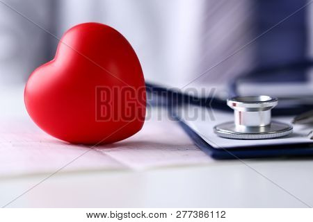 Medical Stethoscope Head And Red Toy Heart Lying On Cardiogram Chart Closeup. Cardio Therapeutist Pu