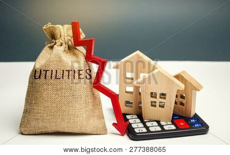 Money Bag With The Word Utilities And An Arrow Down And Wooden Houses On The Calculator. Reduced Pri