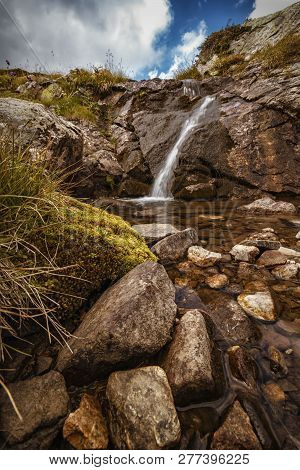 A Beautiful Mountain Landscape With A Brook And A Small Waterfall