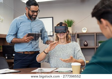 Mature executive man holding tablet showing video to woman wearing virtual glasses at office. Happy smiling client trying virtual reality in office with business team.
