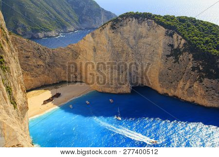 Beautiful View On Shipwreck Beach In Bay, Boats And Ships With Swimming People In Ionian Sea Blue Wa