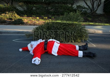 Crime Scene.  Santa Claus lays dead on the ground with a Police Chalk Line and Sheriff Do Not Cross Yellow Crime Scene Tape. Christmas Crime Scene.