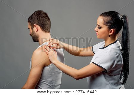 Physiotherapist Woman In White Gown Examining Mans Back Isolated On The Grey Background. Medical Che