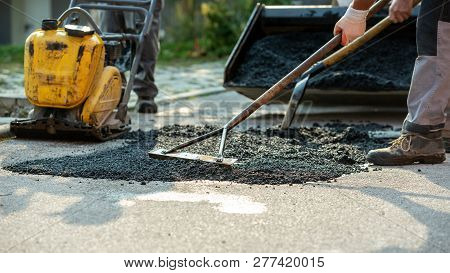 Low Angle View Of Two Workers Arranging Fresh Asphalt Mix With Rakes And Shovel To Patch A Bump In T