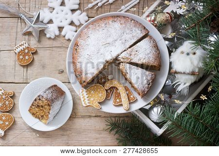 Traditional Christmas Fruitcake On The Background Of A Box With Christmas Toys And Fir Branches.